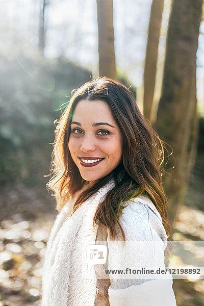 Porträt einer schönen lächelnden Frau im Herbstwald
