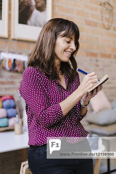 Lächelnde Frau im Strickstudio macht sich Notizen