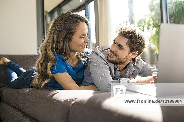 Lächelndes Paar mit Laptop zu Hause auf dem Sofa liegend