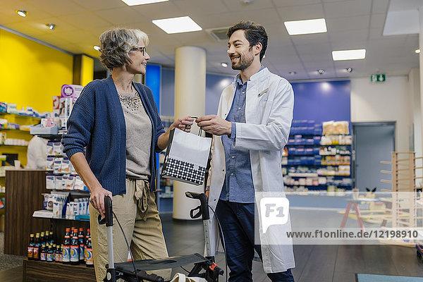 Apotheker  der dem Kunden mit einem Rollator in der Apotheke einen Beutel mit Medikamenten gibt