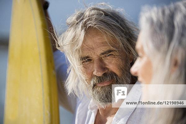Liebevolles Seniorenpaar mit Surfbrettern am Strand