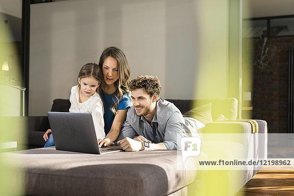 Familie mit Laptop auf dem Sofa zu Hause