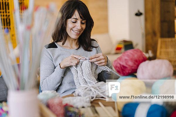 Smiling woman at table knitting