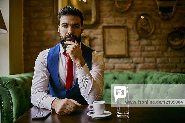Porträt eines modischen jungen Mannes auf der Couch im Café