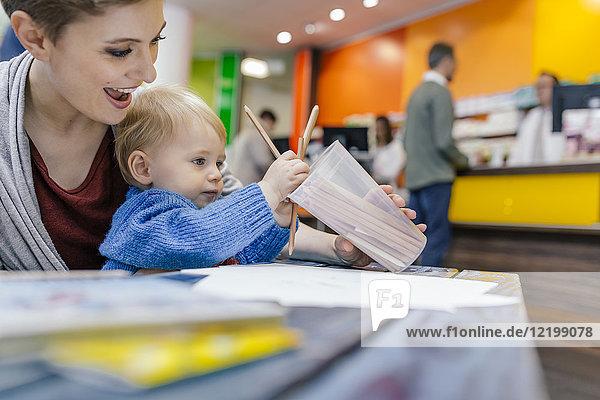 Kleiner Junge mit Mutterzeichnung bei Tisch in der Apotheke