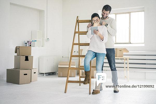 Lachendes Paar an der Leiter im neuen Zuhause mit Blick auf das Tablett