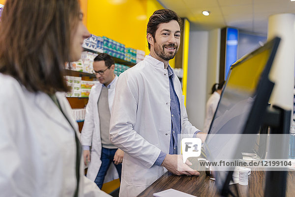 Porträt eines lächelnden Apothekers mit Kollegen an der Theke in der Apotheke