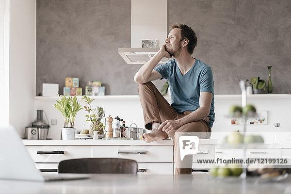 Smilingg Mann sitzend auf Küchentheke mit Blick in die Ferne
