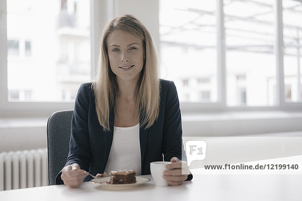 Portrait of smiling businesswoman having coffee and cake at desk in the office
