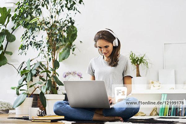 Junge Frau zu Hause sitzend auf dem Boden mit Laptop und Musik hören