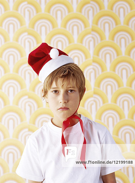 Portrait of boy in bad mood wearing Christmas cap