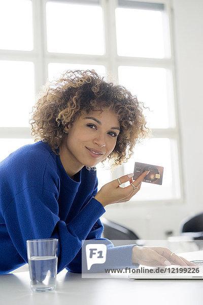 Porträt einer lächelnden Frau mit Kreditkarte zur Bezahlung ihrer Online-Bestellung
