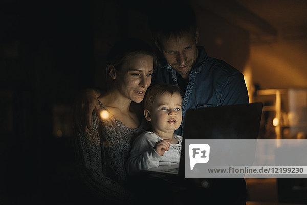 Familie mit Laptop im Dunkeln