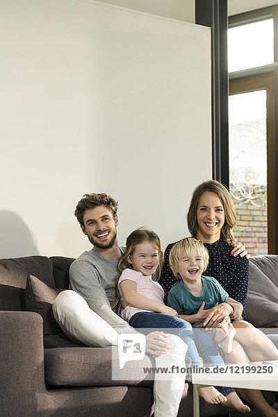 Porträt einer glücklichen Familie  die zu Hause auf dem Sofa sitzt.