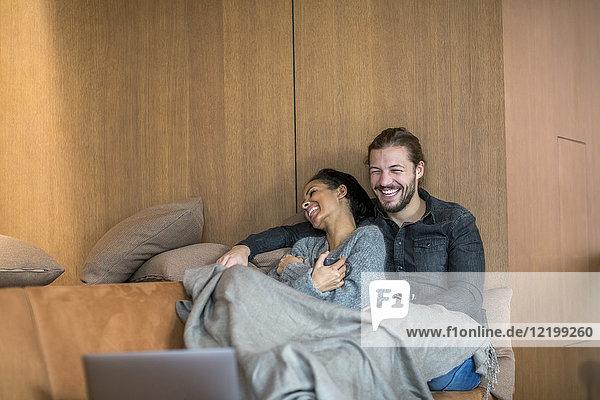 Lachendes junges Paar  das sich gemeinsam auf der Couch ausruht