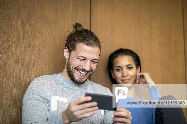 Porträt eines lachenden Mannes beim Anblick des Handys