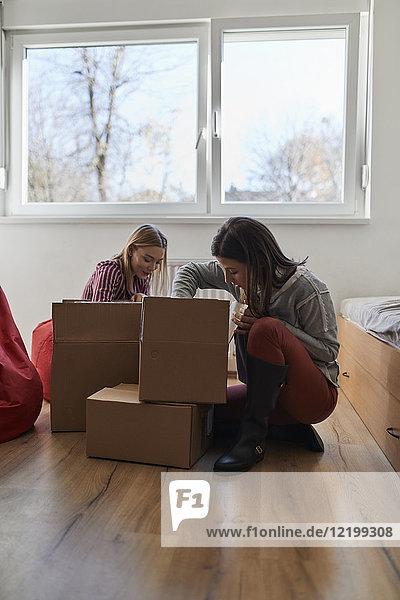 Zwei junge Frauen beim Auspacken von Kartons im Zimmer