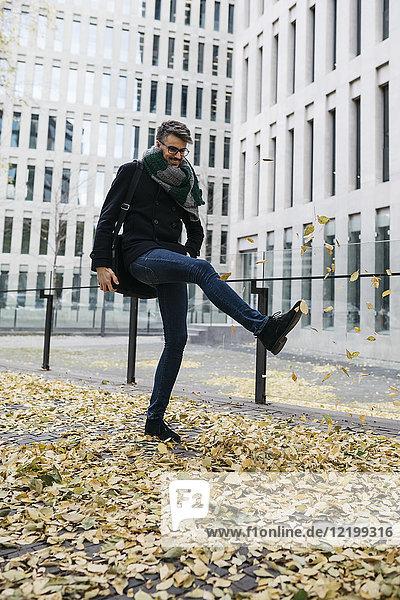 Geschäftsmann spielt mit Herbstlaub in der Stadt