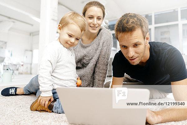 Familie mit Laptop auf dem Boden