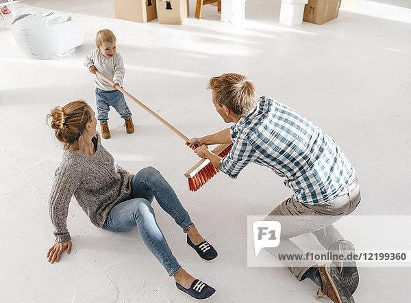 Vater und Tochter amüsieren sich mit einem Besen im Loft