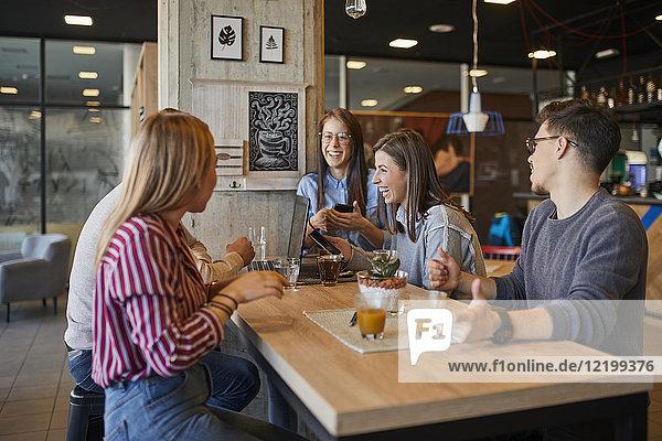 Gruppe von glücklichen Freunden sitzen zusammen in einem Café mit Laptop  Smartphone und Getränken.