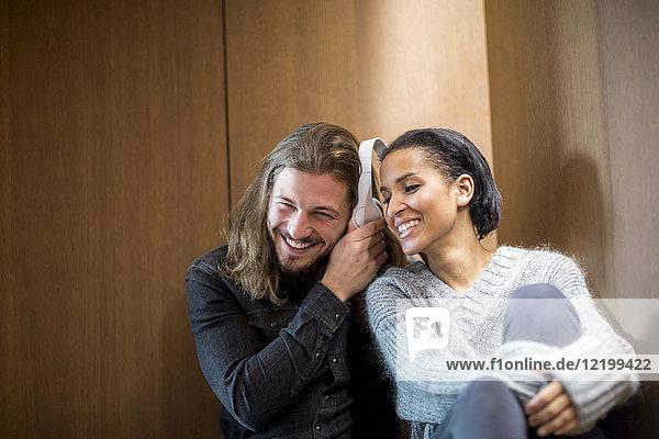 Portrait des glücklichen Paares beim Musikhören mit Kopfhörern