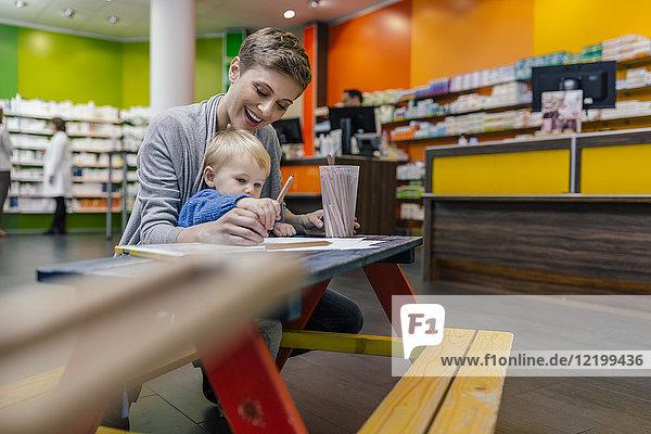 Kleiner Junge mit Mutter auf Bank in der Apotheke