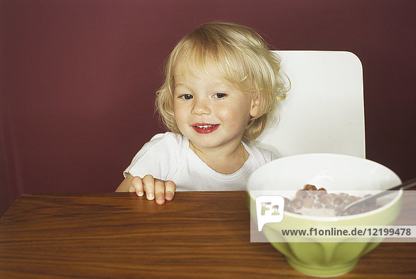 Portrait of smiling little boy at breakfast table