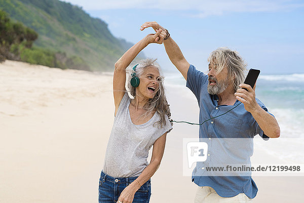 Hübsches Seniorenpaar mit Kopfhörern am Strand tanzend
