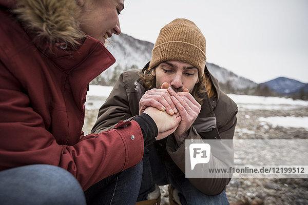 Paar auf einer Reise im Winter mit einem Mann  der die Hände einer Frau wärmt.