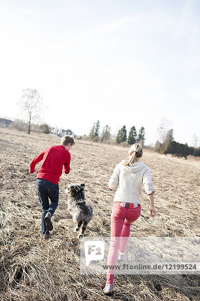 Man and woman with dog running on field