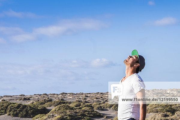 Mann steht in Dünenlandschaft mit geschlossenen Augen