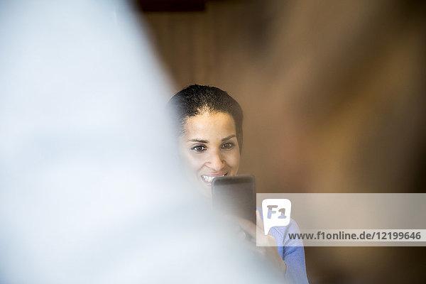 Porträt einer lachenden Frau beim Fotografieren mit dem Handy