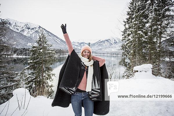 Porträt einer glücklichen jungen Frau in alpiner Winterlandschaft mit See