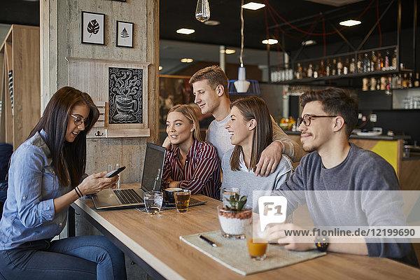 Gruppe von Freunden sitzen zusammen in einem Cafe mit Laptop  Smartphone und Getränken