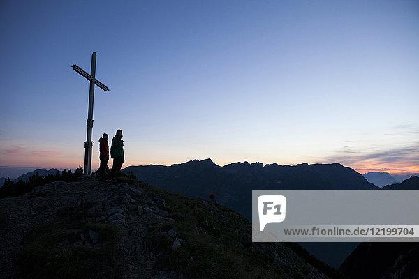 Österreich  Tirol  zwei Wanderer stehen am Gipfelkreuz