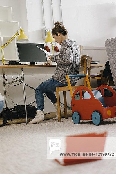 Frau sitzt zu Hause am Schreibtisch  umgeben von Spielzeug.