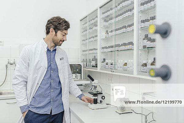 Lächelnder Mann mit Mikroskop im Labor