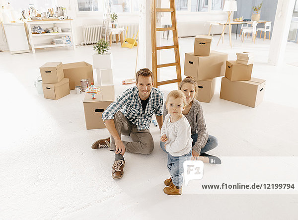 Porträt einer lächelnden Familie beim Einzug in ein neues Zuhause