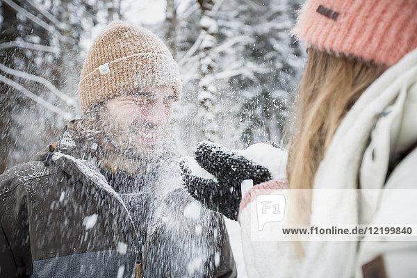 Glückliches Paar beim Schneevergnügen in der Winterlandschaft