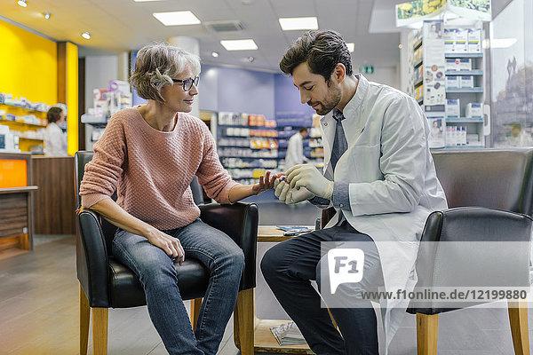 Apotheker misst Blutzucker des Kunden in der Apotheke