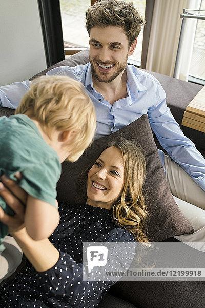 Glückliche Eltern spielen mit dem Sohn auf dem Sofa zu Hause