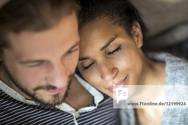 Porträt einer jungen Frau mit Kopf auf der Schulter ihres Partners