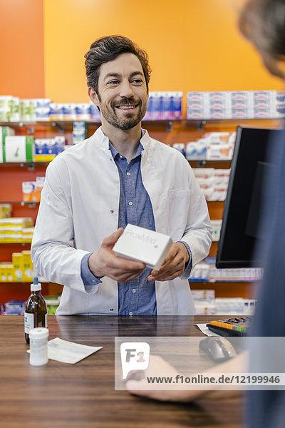 Apothekerin erklärt dem Kunden in der Apotheke die Medizin