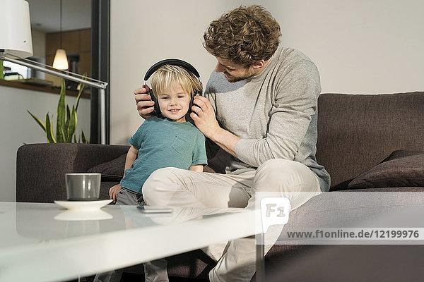 Vater setzt Kopfhörer auf Sohn auf Couch zu Hause auf