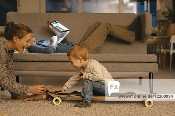 Mutter spielt mit Tochter und Vater mit Laptop im Hintergrund