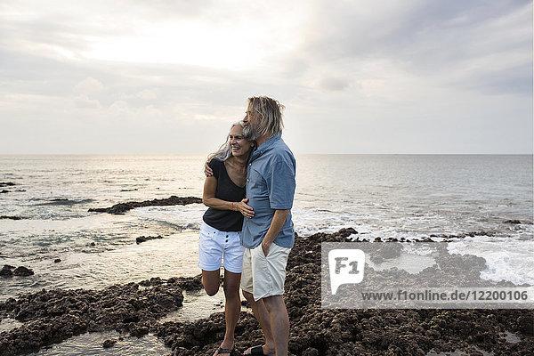 Liebevolles Seniorenpaar  das sich am Meer umarmt