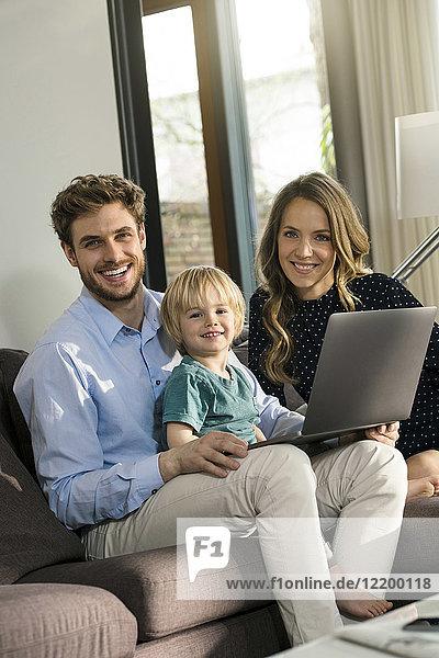 Porträt der glücklichen Eltern und des Sohnes auf dem Sofa mit Laptop zu Hause