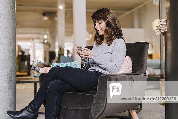 Frau im Sessel sitzend strickend