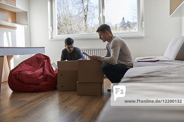 Zwei junge Männer beim Auspacken von Kartons im Zimmer